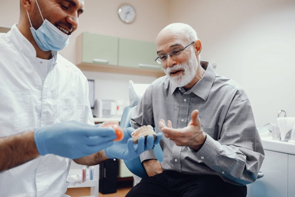 Man with dentist looking at a denture