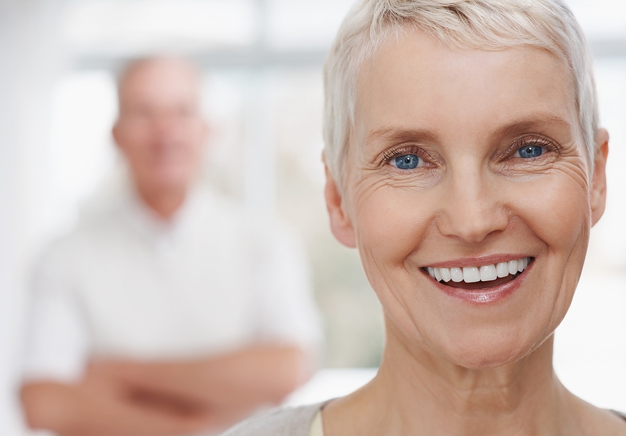 Older woman smiling with man in the background